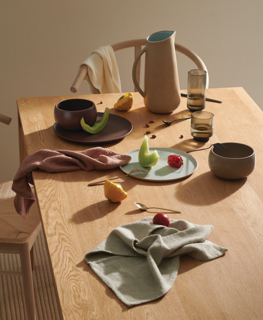 An assortment of beautiful plates and cups rest on a wooden table.