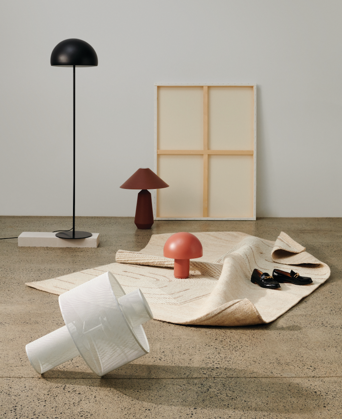A range of short and tall mushroom lamps sit on a concrete floor.