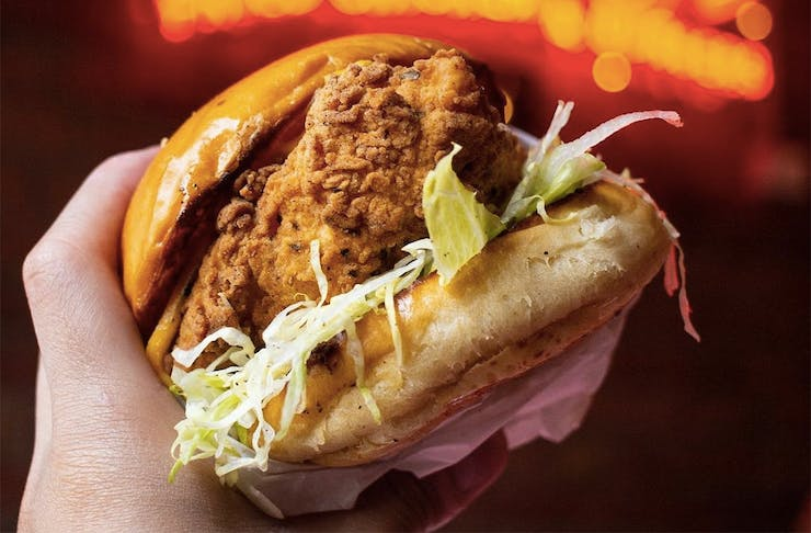 A hand grips a mighty looking chicken burger.
