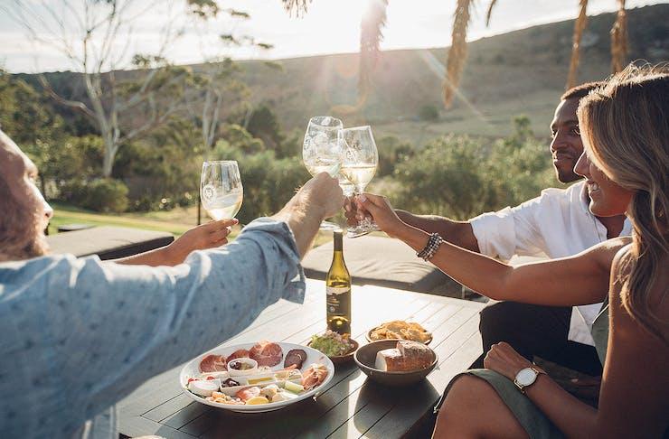 Friends clinking glasses of wine while sitting outside at Stonyridge vineyard on Waiheke