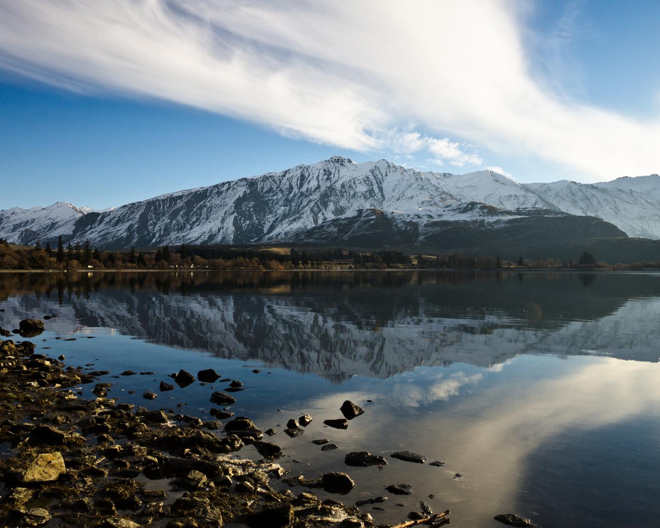 Crystal clear and snowy lake reflection of Glendu Bay