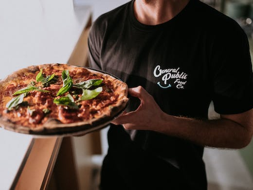 A man with a black t-shirt holding a pizza.