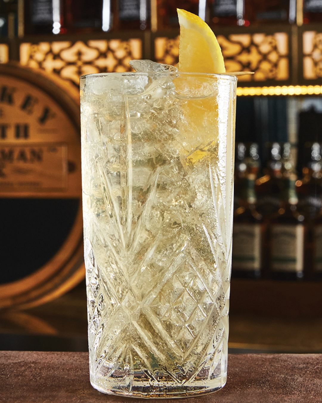 A Gentleman's Highball garnished with a lemon wedge on a bar.