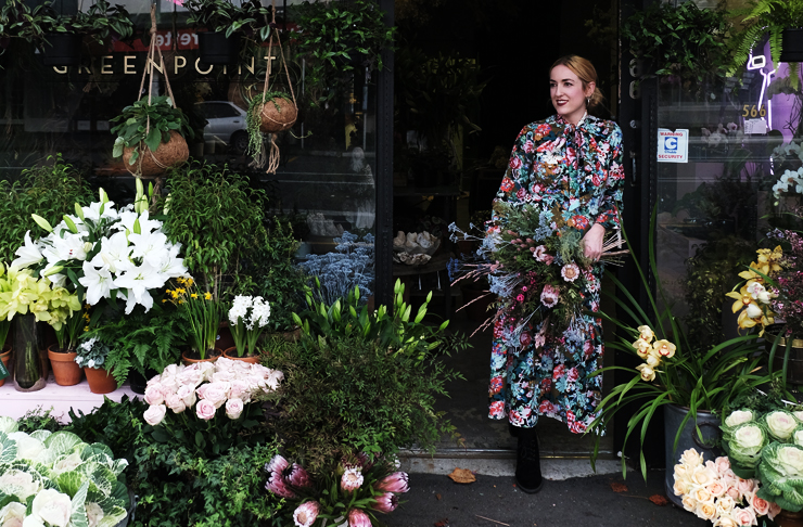 Georgie stands in front of her flower shop, Greenpoint surrounding by flowers and plants. The building is green.