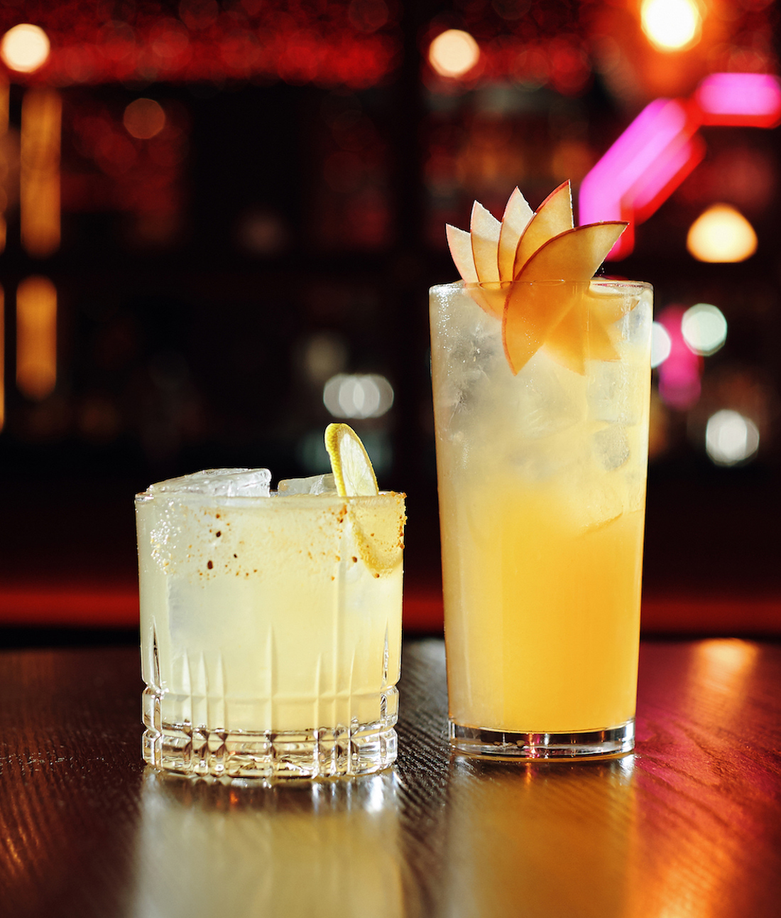 Two yellow-hued cocktails are lined up on the bar.