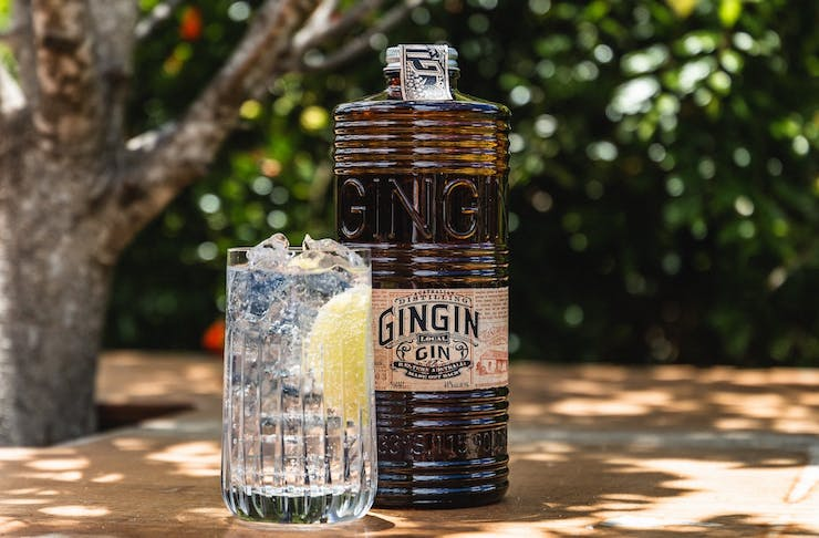 A bottle of Gingin gin next to a glass of gin and tonic