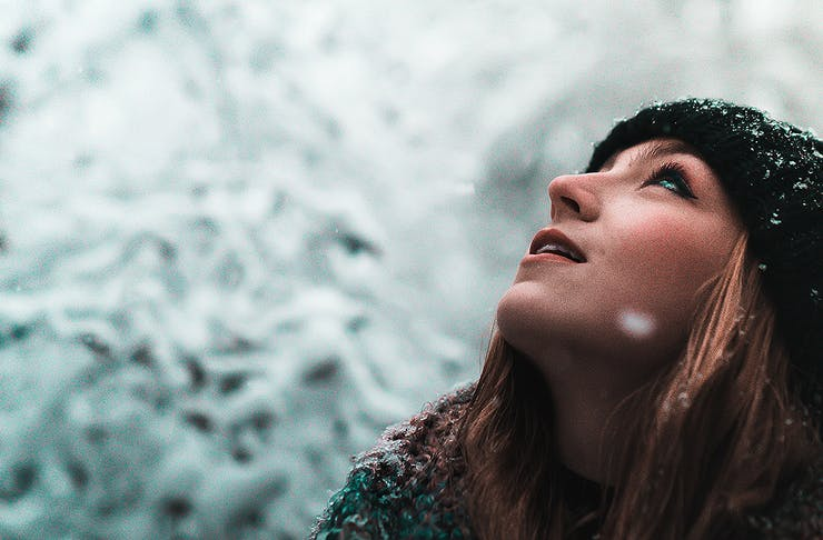 A girl looks up in the snow, wrapped up against the elements.