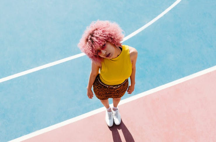 A girl stands on a court looking up at the camera wearing cool clothes.