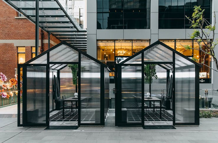 Two glasshouse dining pods outside the Heritage at Brookfield Place