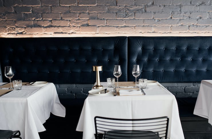 a navy blue bench and tables with white tablecloths