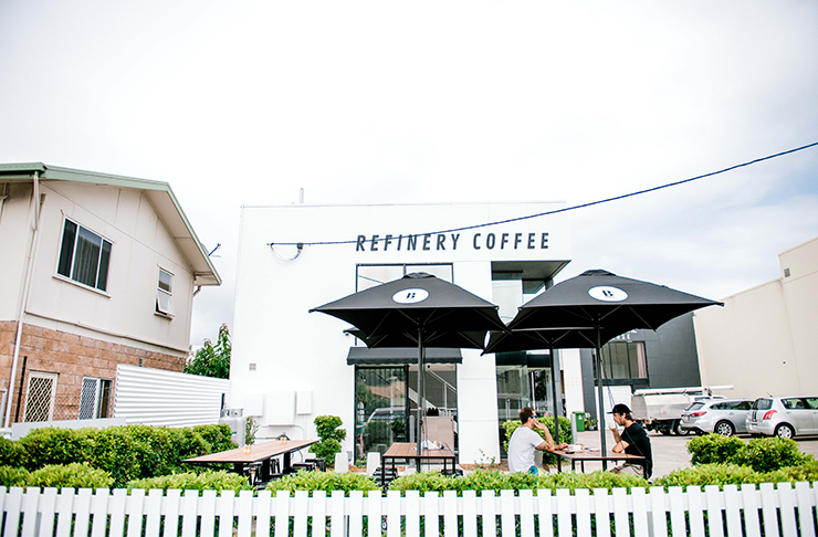 An exterior shot of Currumbin cafe, Refinery Coffee. Outdoor seating with black umbrellas sit out the front of the two-storey, white building.