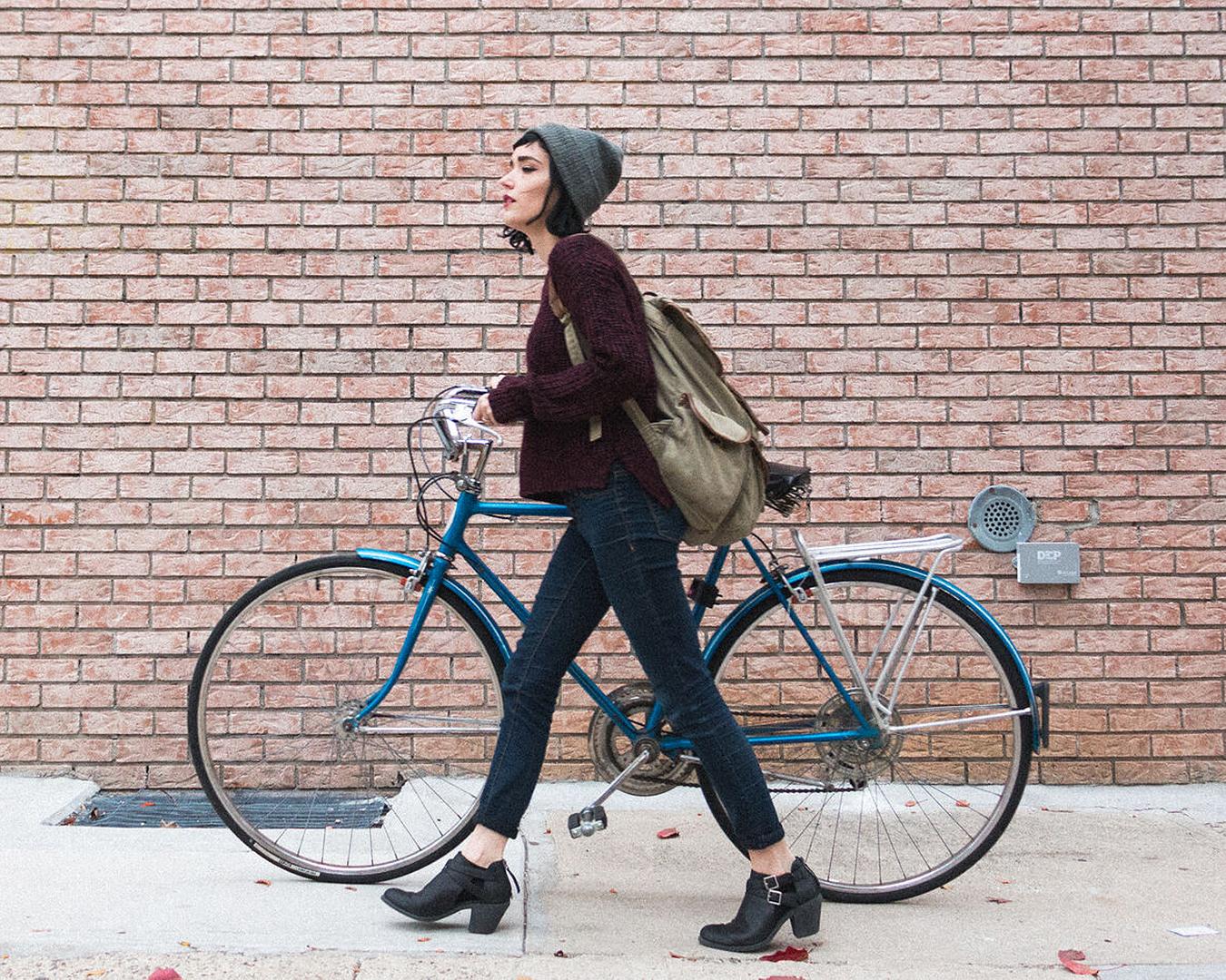 A woman walks while pushing her bike.