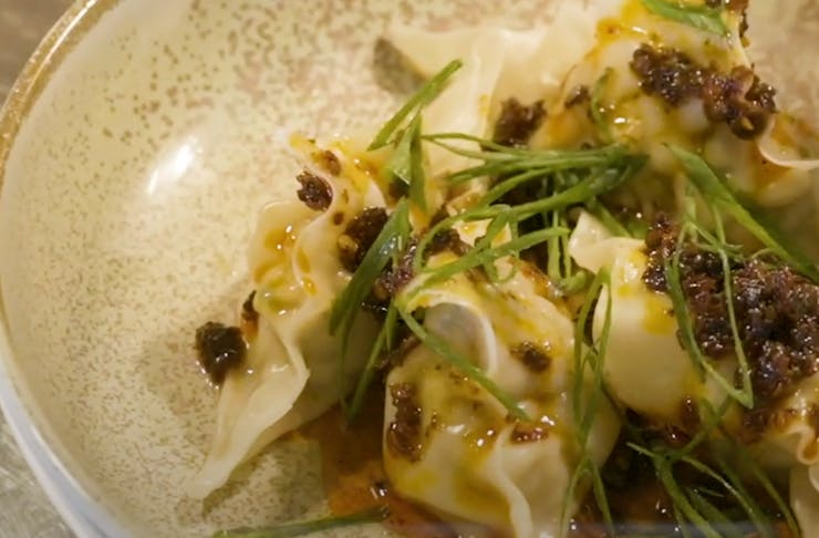 Close up of cooked dumplings in a bowl, topped with spring onion and sauce