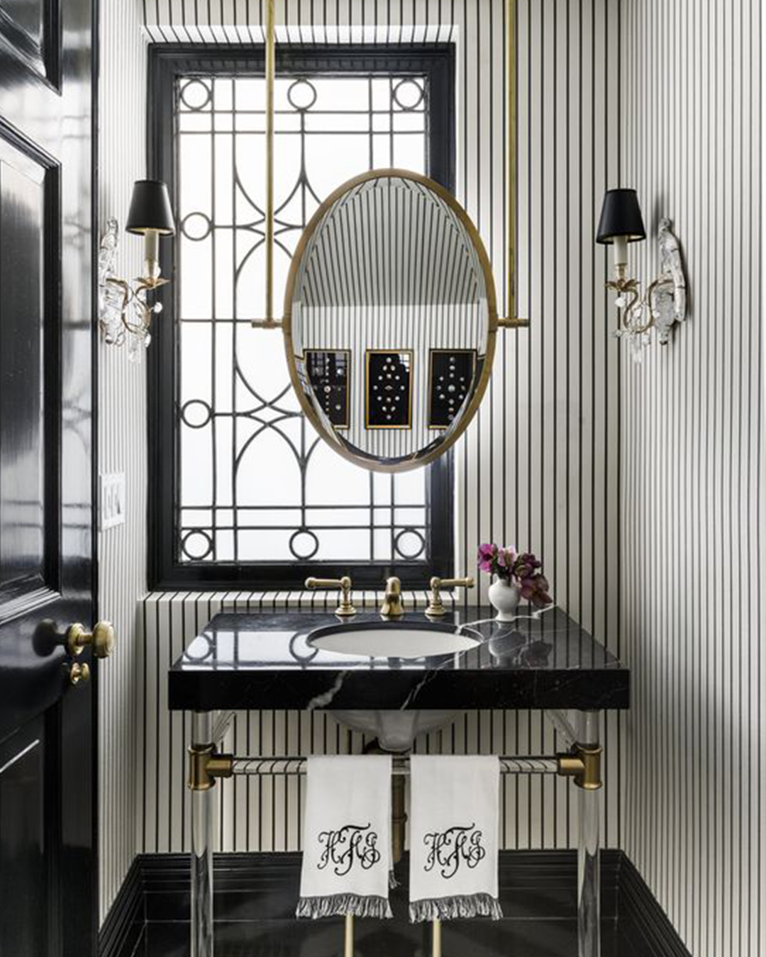 Grand Millenial style bathroom with gold oval mirror, striped wallpaper and black accents