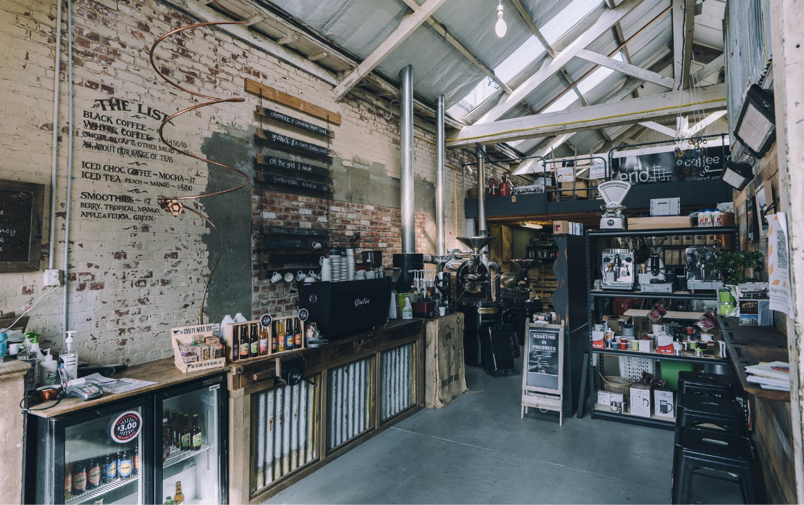 Grid Coffee Roasters, industrial aesthetic building with a variety of coffee beans stacked on the shelves