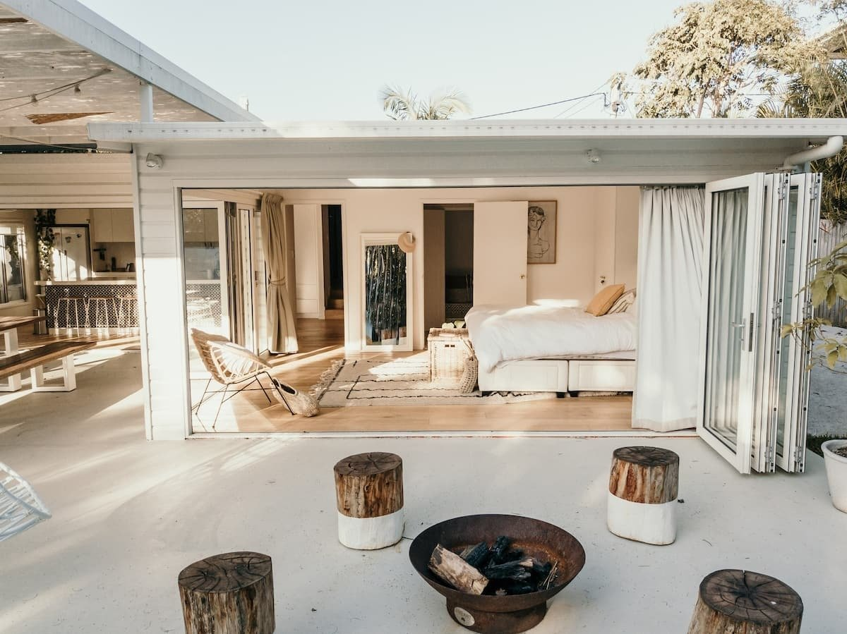 stools around a firepit in front of an open bedroom