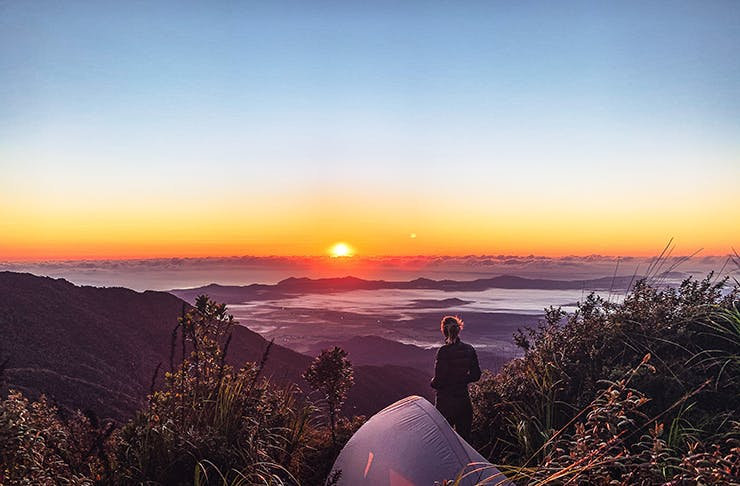A woman on top of a hill with a tent looking at a sunset.