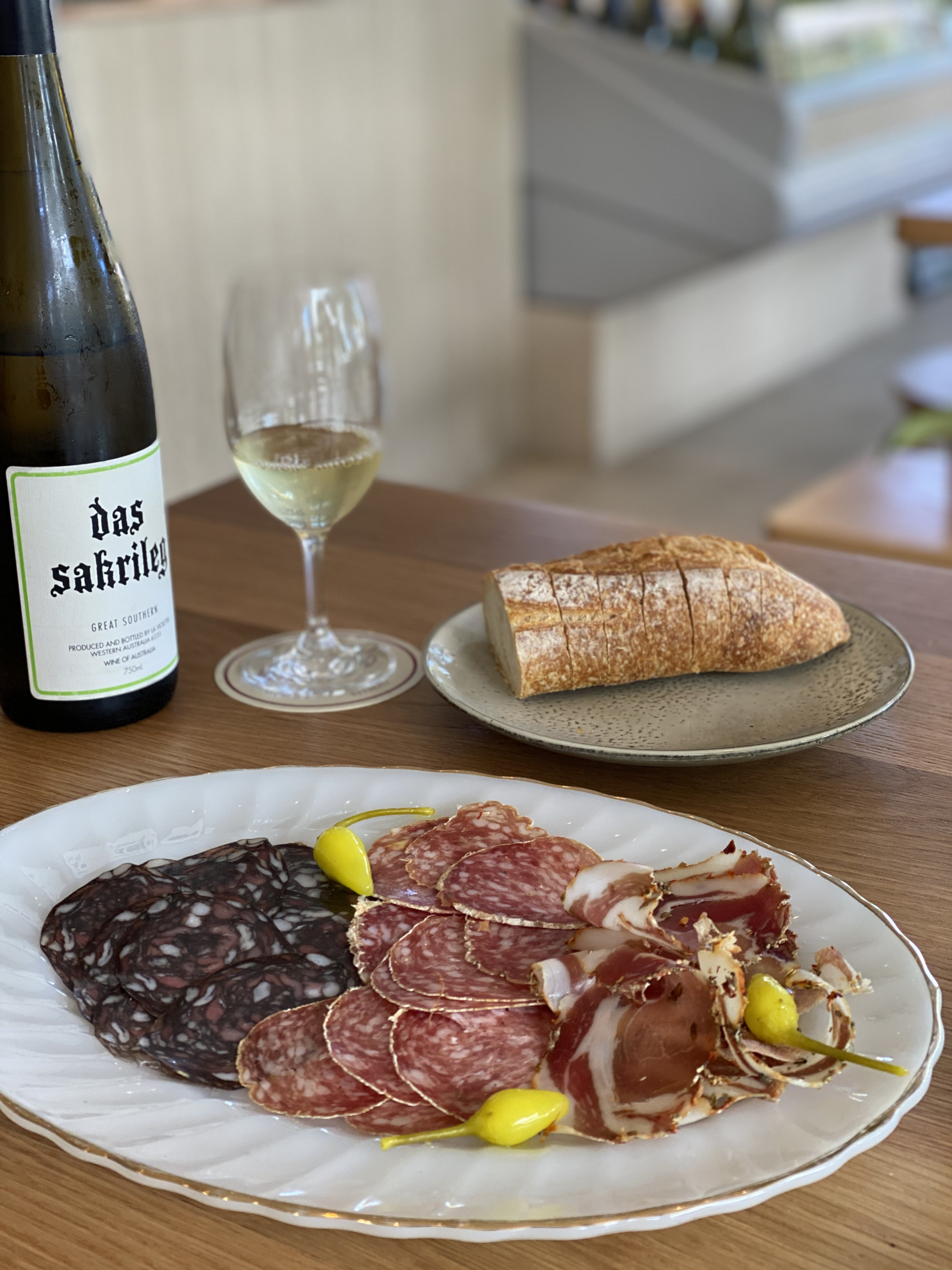 a generous salumi plate with a glass and a bottle of white wine in the background