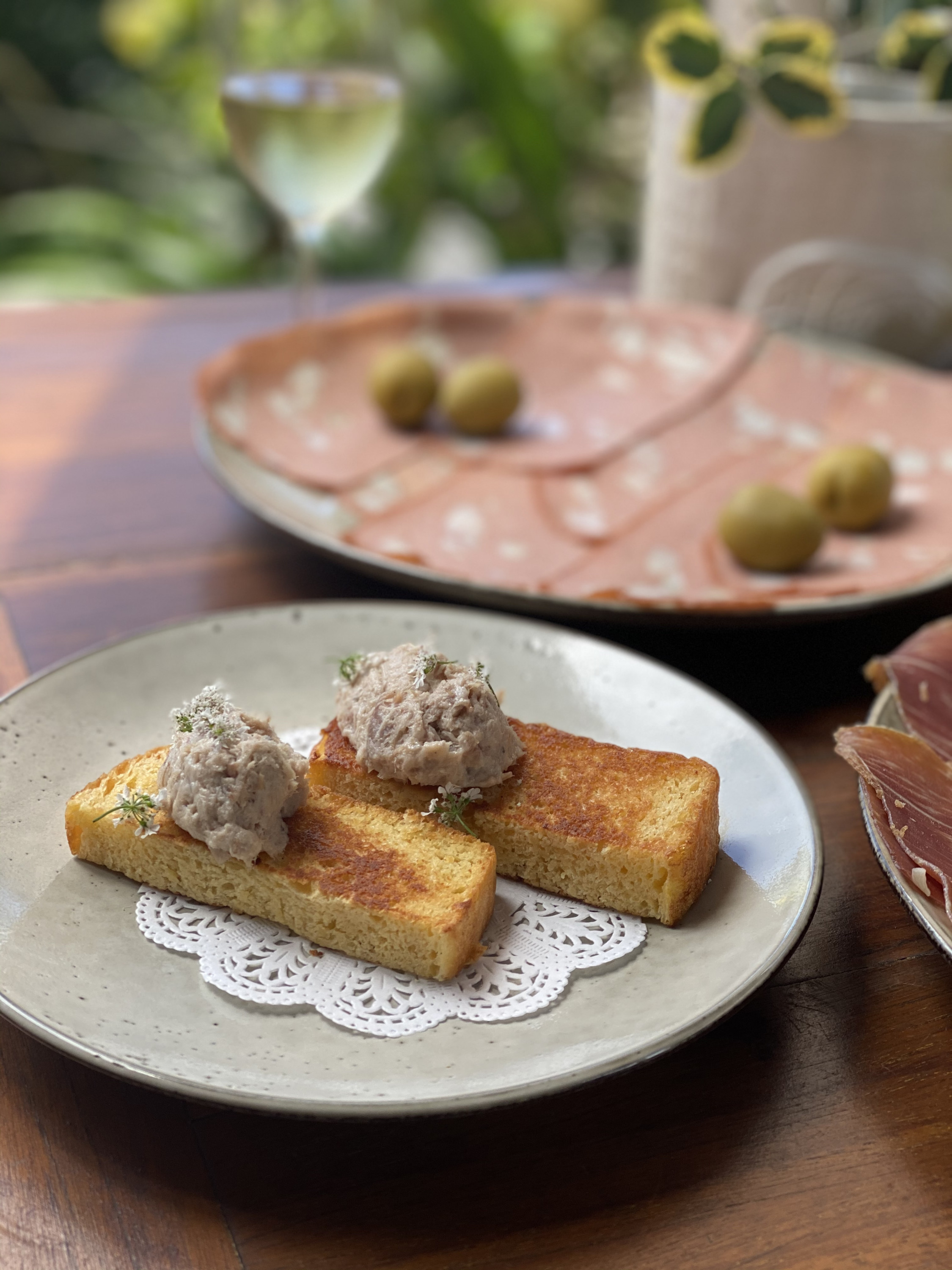 a pork rilette dish with a wine glass in the background