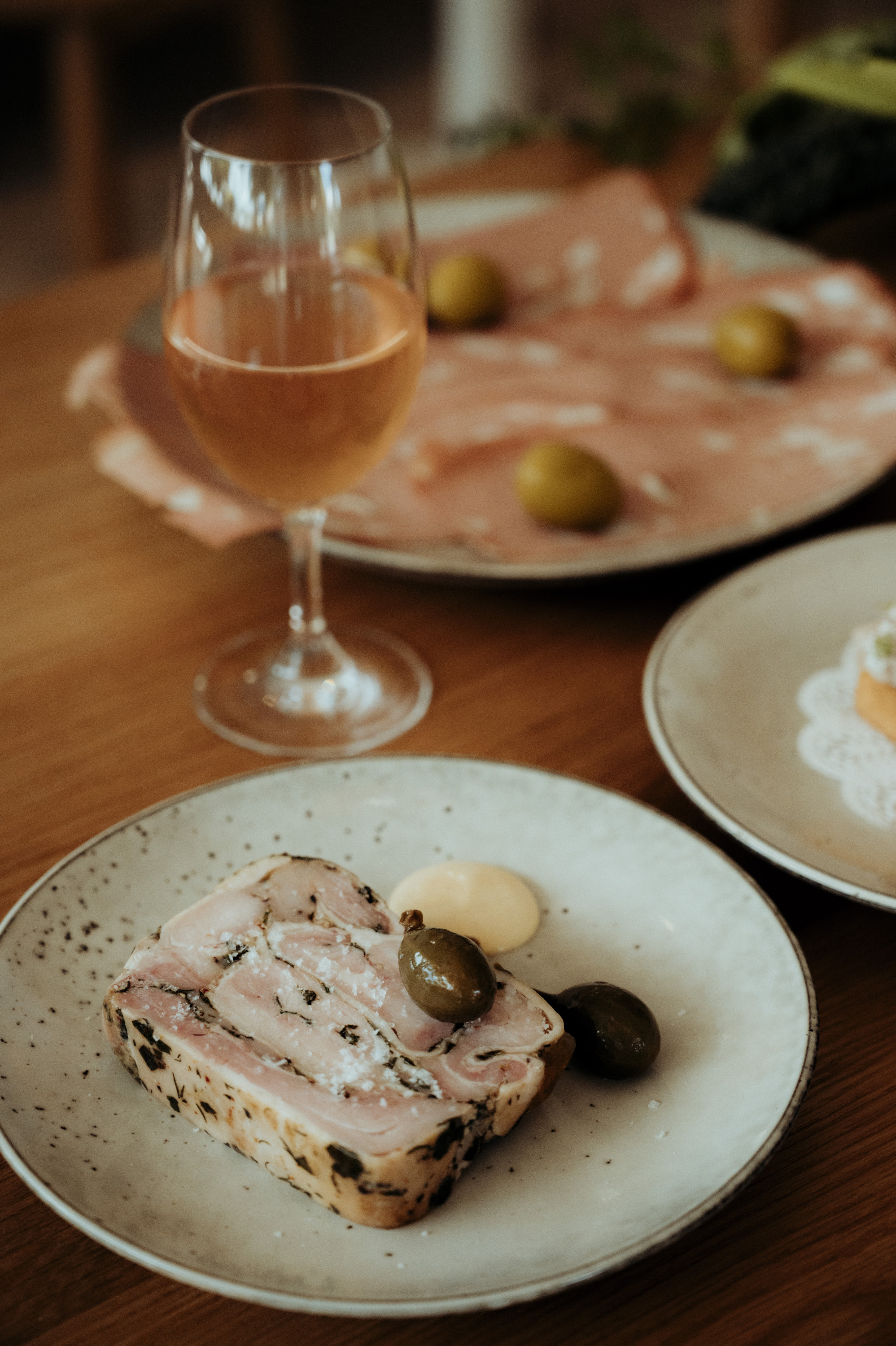 a glass of rose and scattered salumi plates