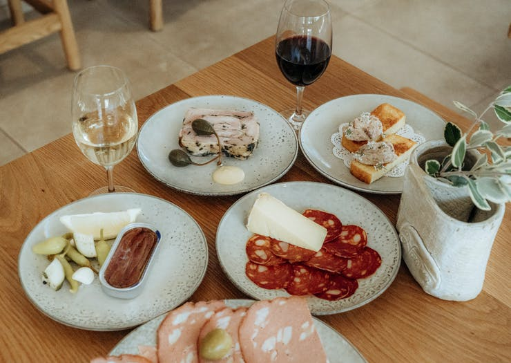 a table full of various plates with salumi and aperitivo dishes with a glass of wine