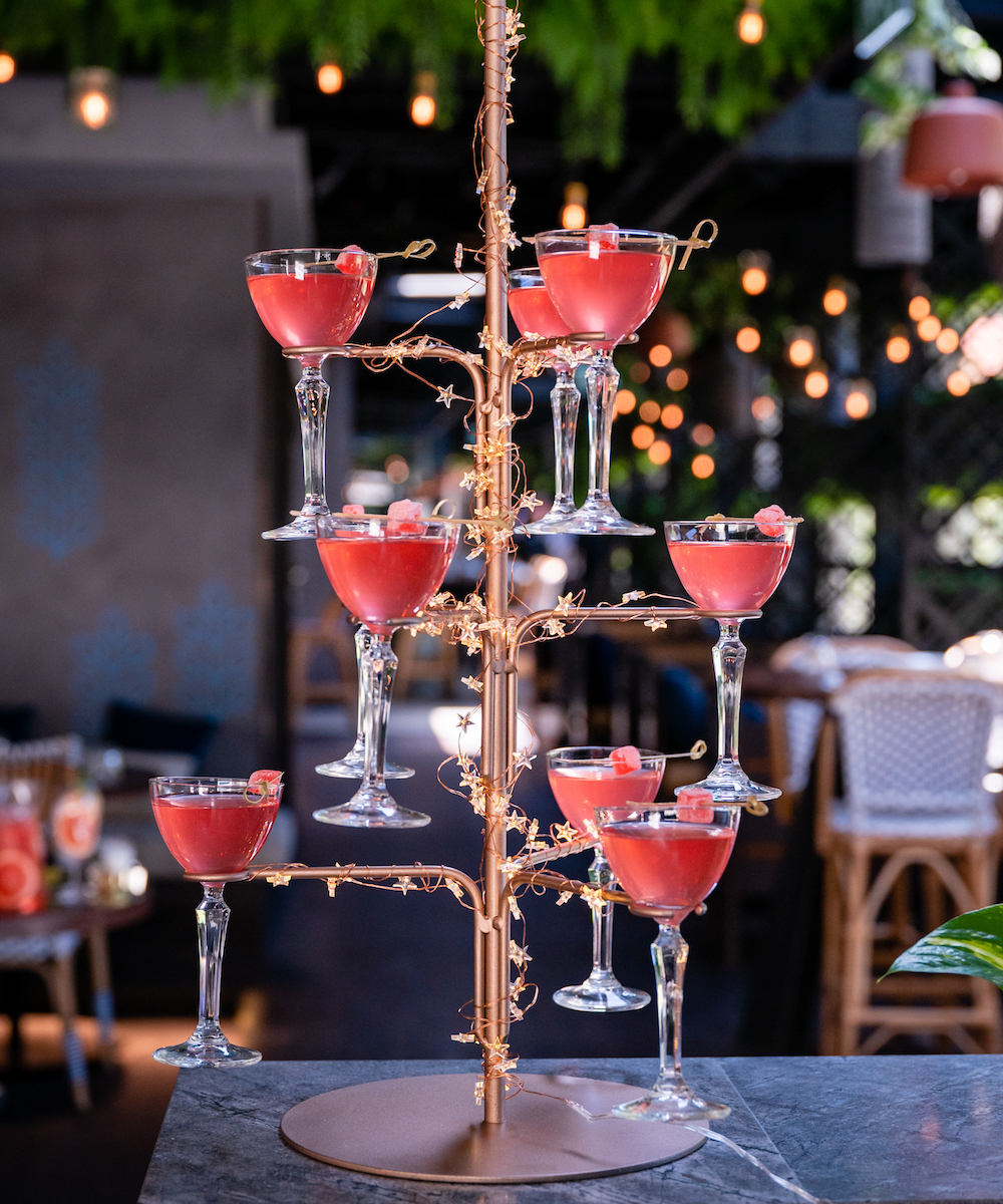 A gold tower filled with pink Turkish delight martinis, wrapped with gold wire and stars