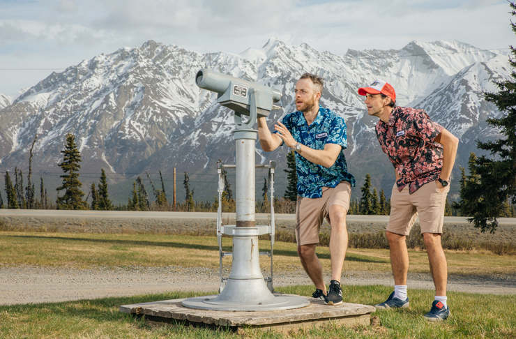 Hamish and Andy stare into a telescope whilst standing in front of snowy mountains