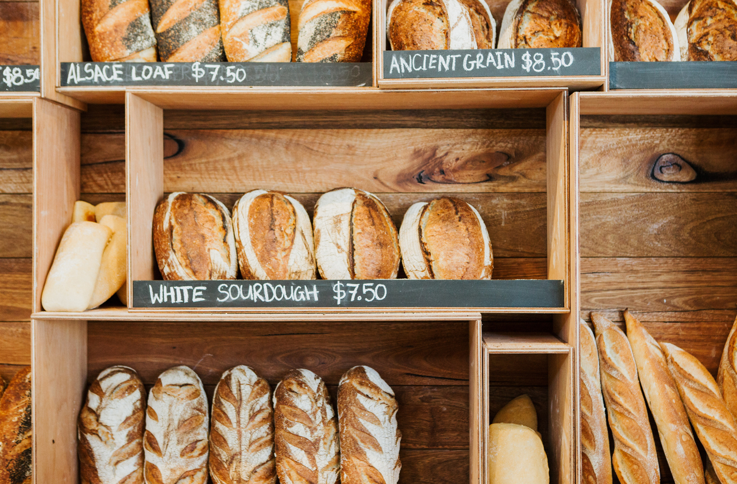 A wall of timber shelves filled with freshly baked bread at a Sunshine Coast bakery.