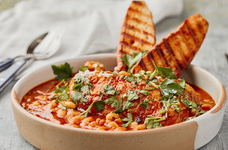 A hearty chicken cassoulet dish is topped with baked beans, bread and parsley.