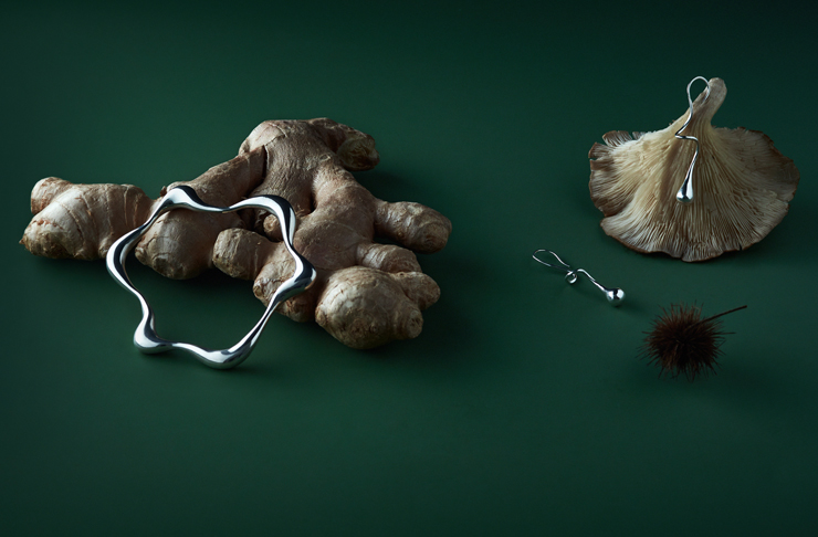 A piece of Hera Saabi jewellery lays on top of a piece of ginger, both against a green backdrop