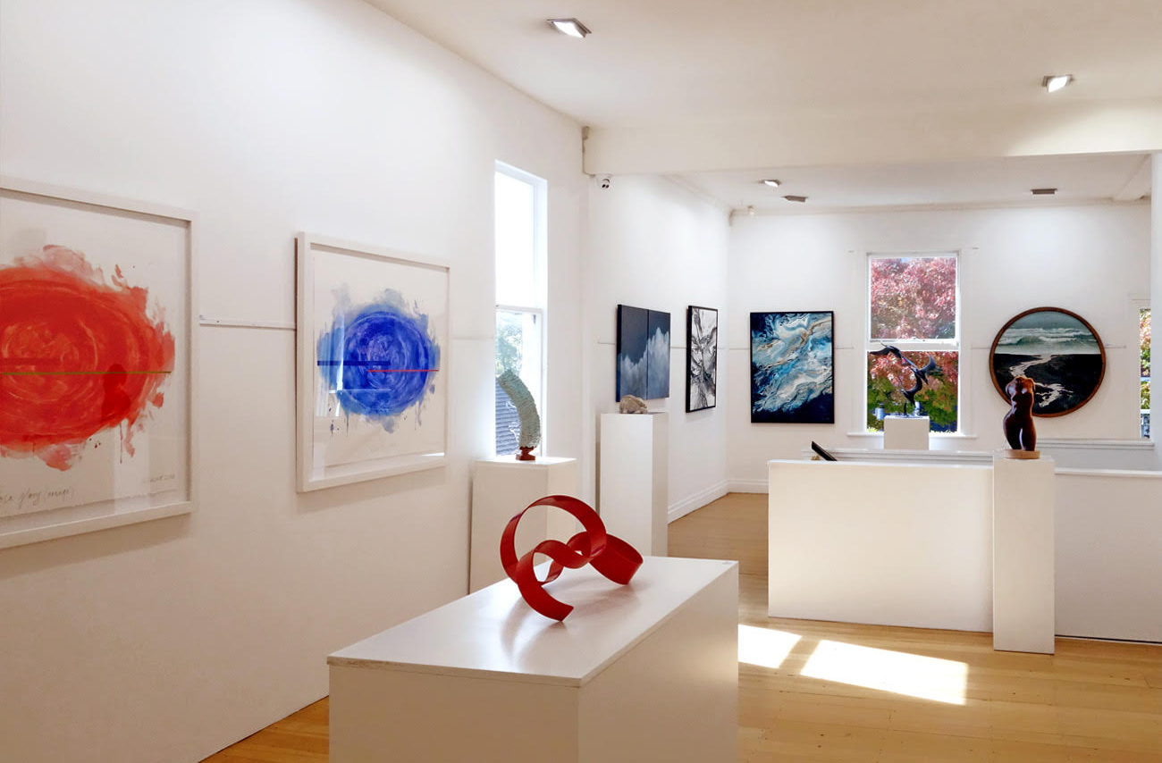A clean and elegant white gallery space with various abstract paintings and sculpture pieces.