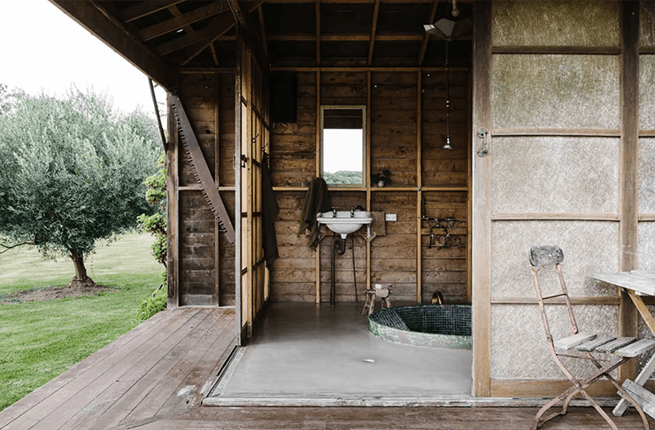 The outdoor bath house on the edge of the house with wooden doors and walls.