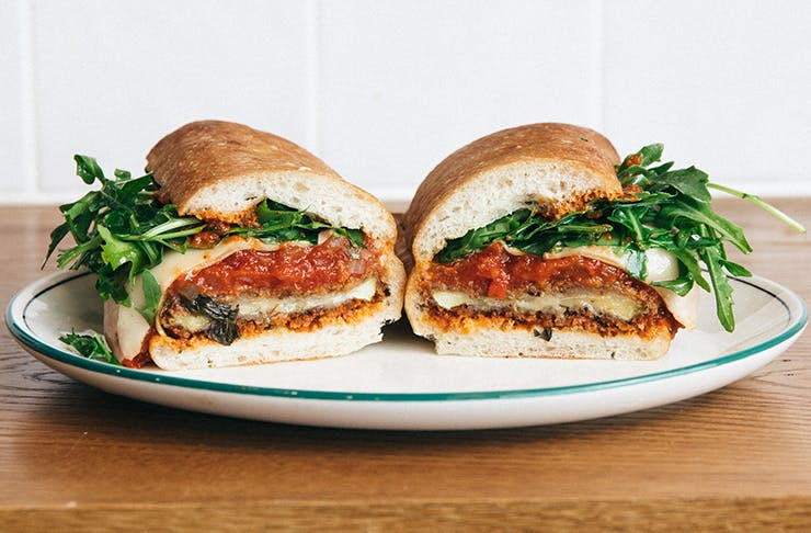 A sandwich filled with rocket, Napoli sugo, cheese, and eggplant.