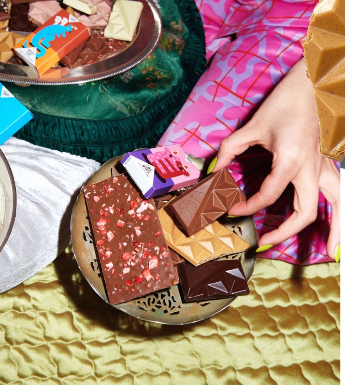 A hand reaches for a full plate of delicious Hey Tiger Co chocolate.