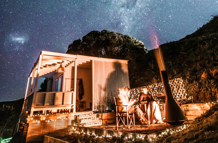 two people sit in front of an outdoor fire at night whilst every star in the universe can be seen in the night sky. The tiny home to the left is lit up with fairy lights.