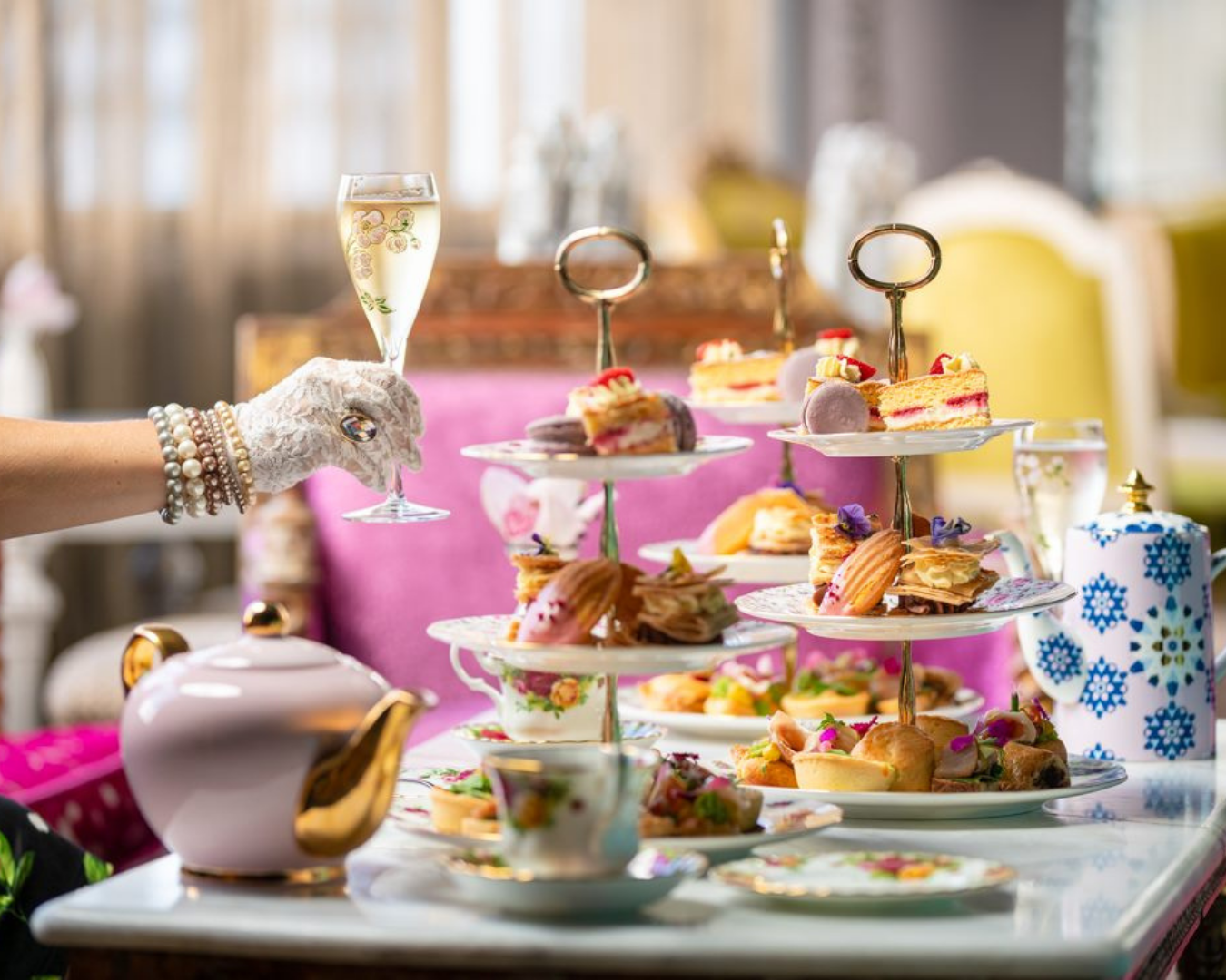 A lady holding a glass of bubbles next to a beautiful display of food and beverages at a high tea