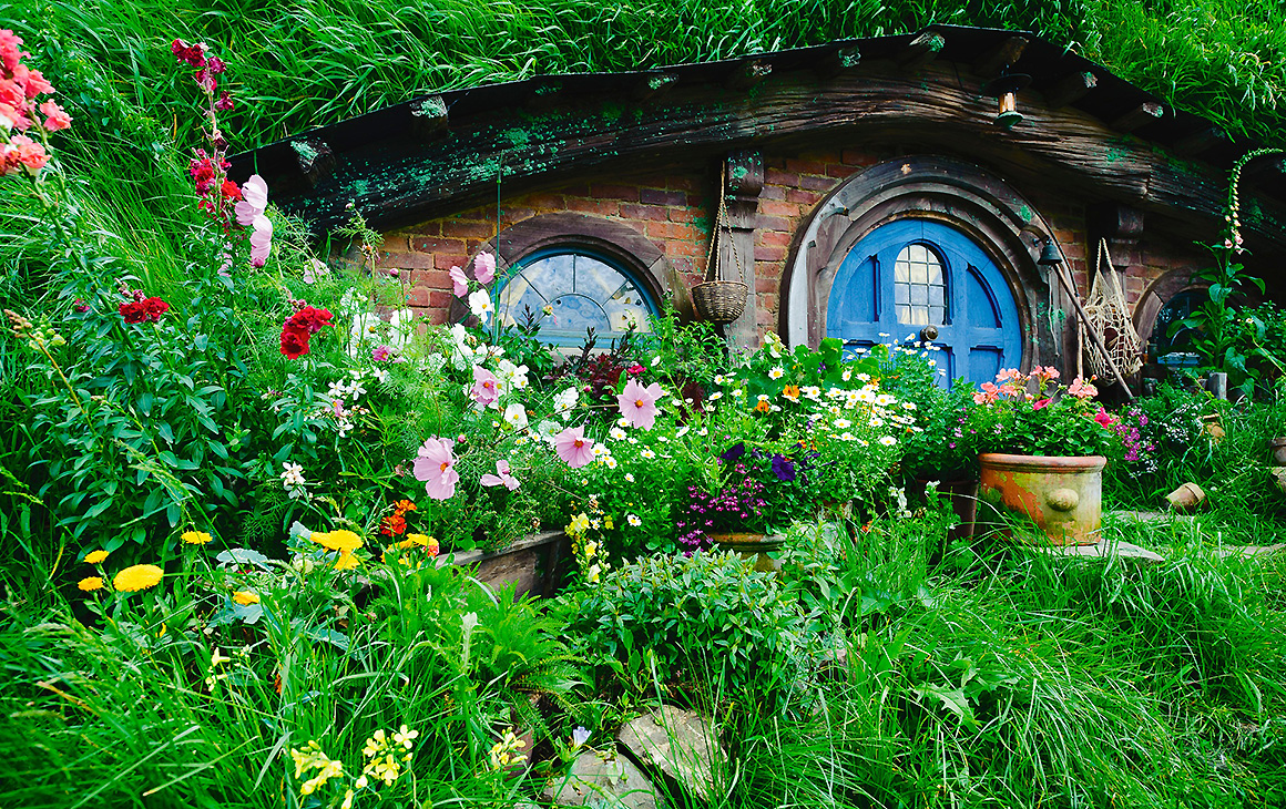 A hidden doorway surrounded by lush green vegetation and flowers at Hobbiton, one of New Zealand's top tourist attractions.