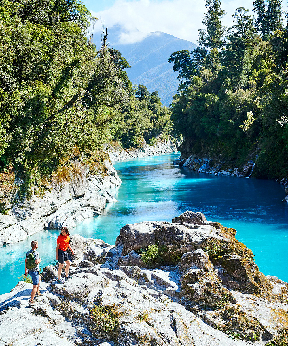 A stunning view of Hokitika Gorge with people scrambling over the rocks.