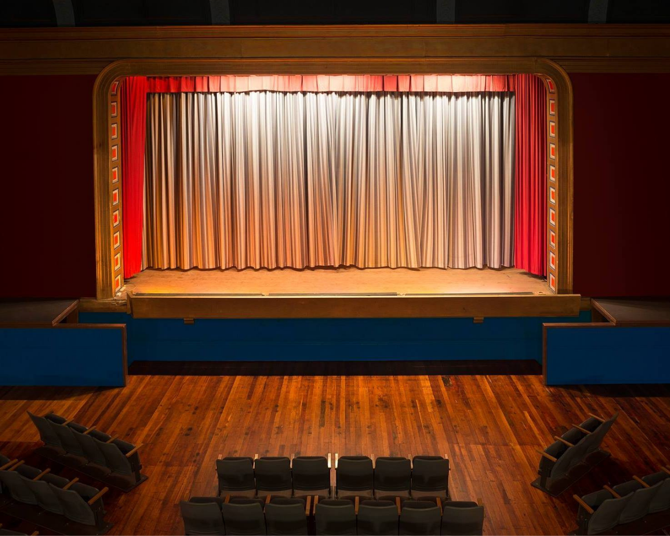 An empty theatre with curtains drawn and spotlight on stage