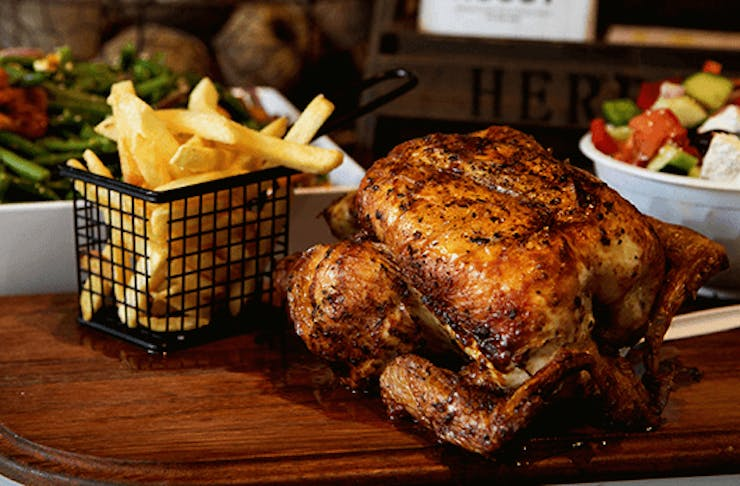 A roast chicken on a board with some chips