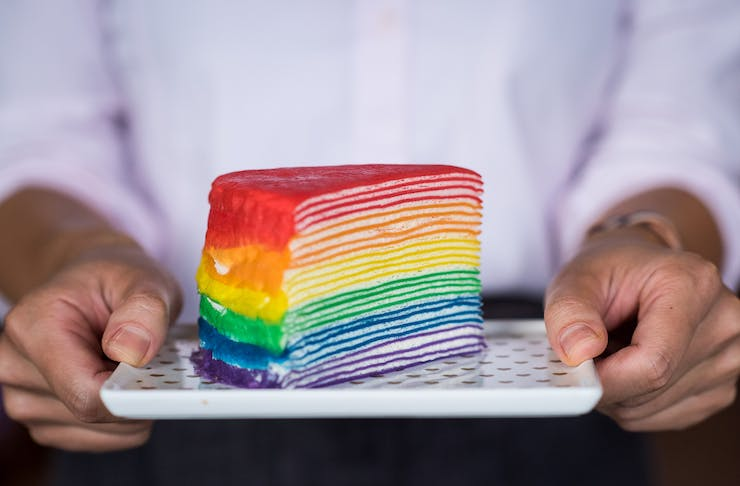 A close up of a person holding a rainbow layered cake out in front of them