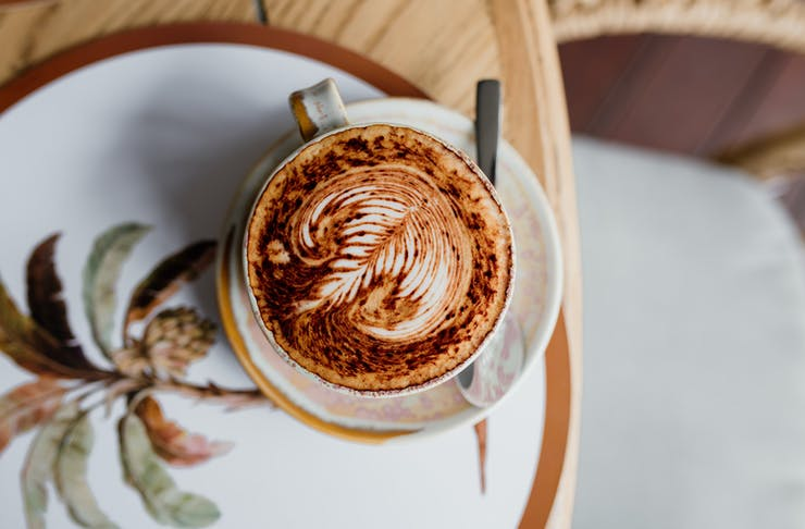 a coffee atop a plate with palm trees