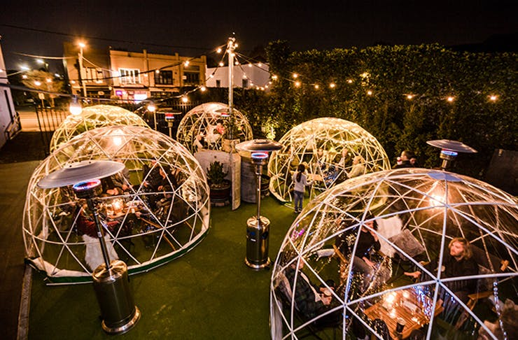 A group of outdoor Igloos filled with people underneath fairy lights.