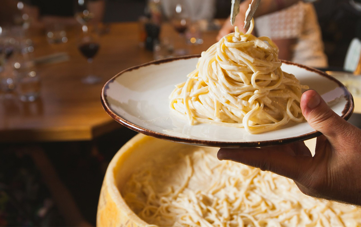 Pasta in a wheel of cheese behind a plate of pasta.
