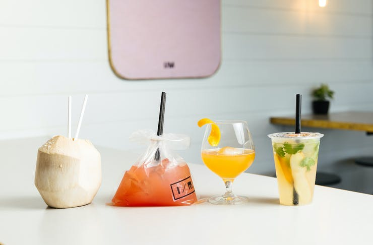 Four cocktails lined up on a bench, one in a coconut, one in a bag and the other two in glasses