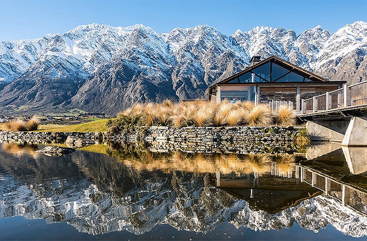 The outside of the clubhouse at Jack's Point shows the stunning Remarkables in the background.