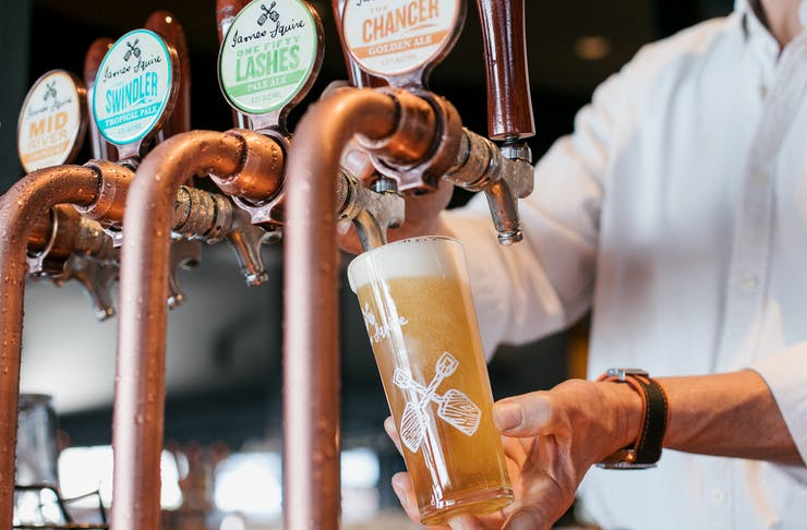 A barman pours a beer into a glass from a copper tap at a James Squire brewhouse.