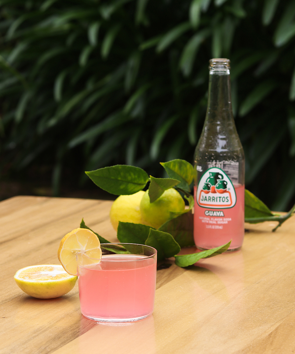 Jarritos Mexican soda sits on a table surrounded by luscious lemons