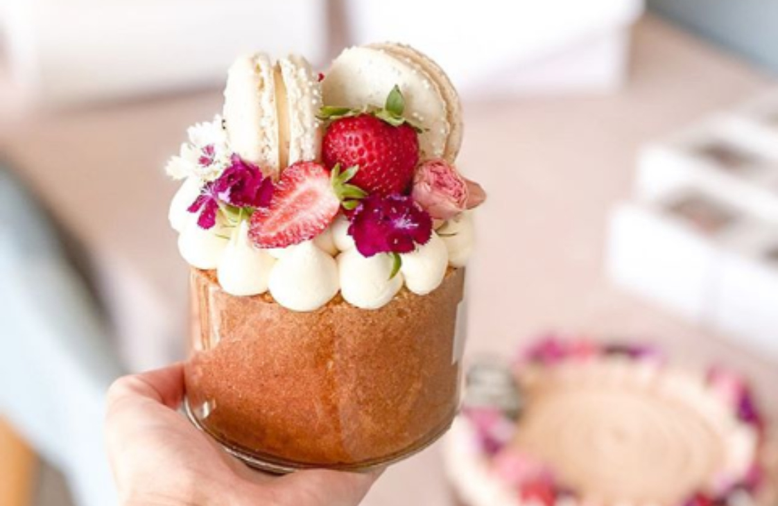 A hand holds a single-serve cake decorated with berries, macarons and flowers.
