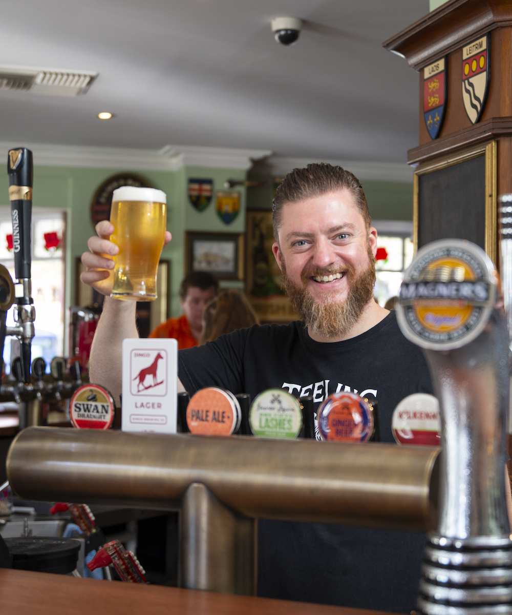 Paul Maloney holding beer behind the bar at Johnny Fox's